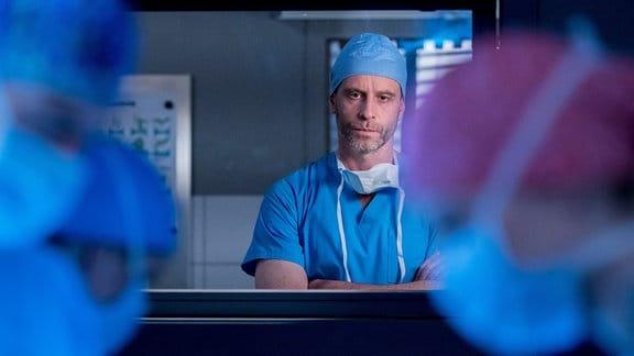 Unter den strengen Blicken von Dr. Kai Hoffmann (Julian Weigend, M.) ist es gar nicht so einfach für Ben Ahlbeck (Philipp Danne, l.) und Julia Berger (Mirka Pigulla, r.) zu operieren.