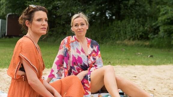 Tatjana (Judith Sehrbrock, l.) und Mona (Jana Hora-Goosmann, r.) sitzen an einem Strand.
