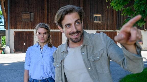 Hannes (Pablo Konrad, r.) zeigt mit seinem linken Zeigefinger auf etwas. Maja (Christina Arends, l.) steht hinter ihm.