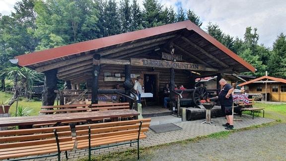 Eine Blockhütte vor einem Wald. Über der Tür steht 'Ranch Dark Mountain', eine US-Südstaaten-Flagge liegt auf einer Bank. Ein Mann grillt, mehrere Personen sitzen auf Bänken vor dem Eingang.