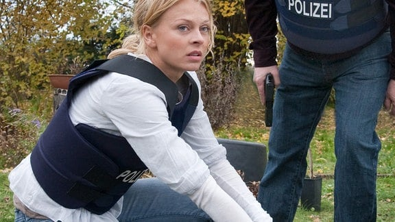 Nora Lindner (Isabell Gerschke) und Schneider (Wolfgang Winkler)  beugen sich über eine Person.