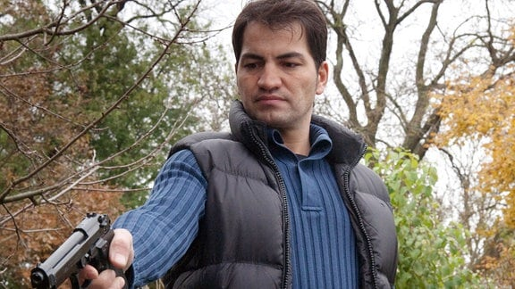 Maik Canavar (Bülent Sharif)richtet eine Handfeuerwaffe nach unten.