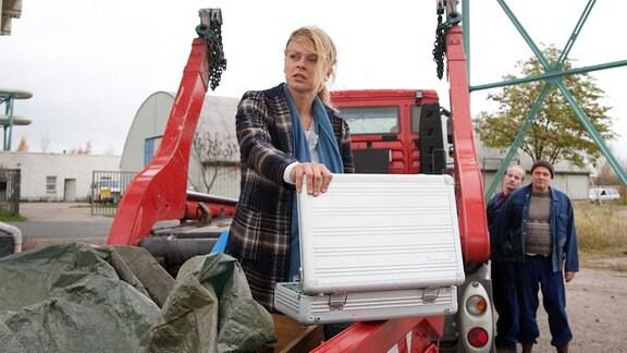 Nora Lindner (Isabell Gerschke) hat einen Metallkoffer geöffnet, blickt aber nicht hinein.