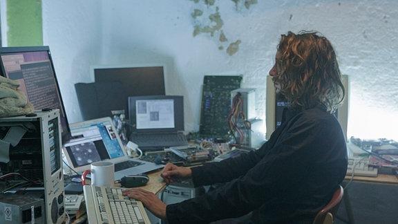 Faust sitzt am Computer. Neben ihm stehen weitere Computer-Endgeräte und diverses Computer-Zubehör.