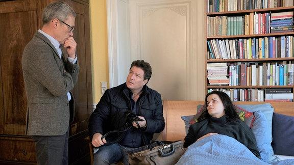 Christian (Francis Fulton-Smith, M.) macht einen Hausbesuch bei Jenny Illner (Maxine Kazis, r.) der es trotz Behandlung sehr schlecht geht.