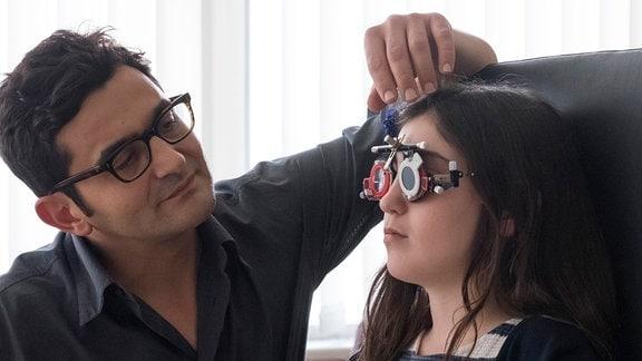 Marie beim Augenarzt Herrn Vergne  Bei der Überprüfung der Sehstärke schummelt Marie (Alix Vaillot, Laurent Capelluto)