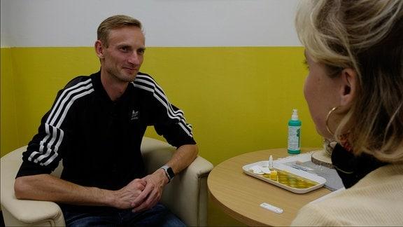 Denis im Gespräch mit MDR-Autorin Marie Landes, auf dem Tisch HIV-Test-Utensilien.