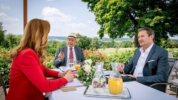 """Bei der Gesellschafterversammlung mit Christoph (Dieter Bach, r.) eröffnet Ariane (Viola Wedekind, l.) Werner (Dirk Galuba, M.), dass sie Lia Geld dafür geboten hat, den """"Fürstenhof"""" zu verlassen."""