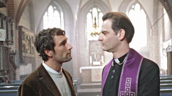 Ein Geistlicher und ein Mann in einer Kirche.