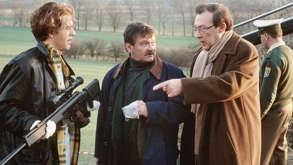 KT Heinz (Stephan Ullrich), Hauptkommissar Schneider ( Wolfgang Winkler), Hauptkommissar Schmücke (Jaecki Schwarz) finden die Tatwaffe am Unfallort. KT Heinz hält das Gewehr in der Hand.