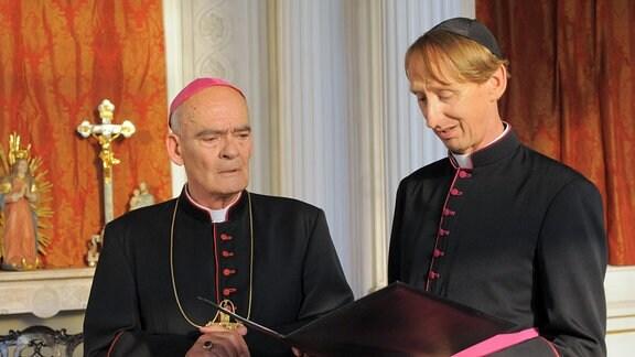 Bischof Hemmelrath und Monsignore Mühlich überlegen, wie sie an mehr Spendengelder kommen.
