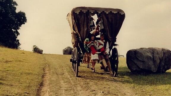 Luisa und Jacob sitzen hinten auf der Kutsche von Röckle, die fort fährt.