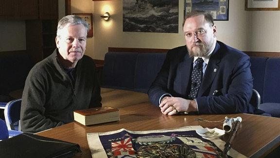 Ulrich Schmidt sitzt mit einem weiteren Mann an einam Tisch auf dem ein Plakat und eine alte Pfeife liegen. Sie schauen in die Kamera.