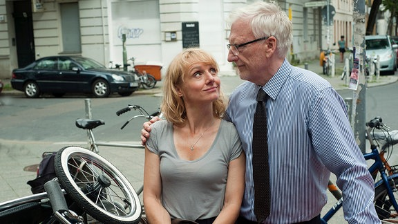 Anton (Ernst Stötzner) und Ehefrau Johanna (Christina Große) erwarten Nachwuchs und versuchen, den Kinderwagen in ihrem Sportwagen unterzukriegen.