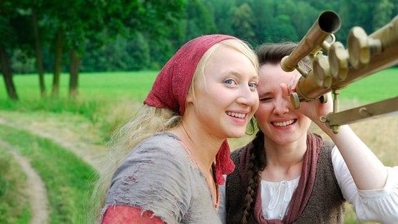 Die kluge Bauerntochter (Anna Maria Mühe) und ihre Freundin die Magd (Sabine Krause) bestaunen das Fernrohr des Königs.