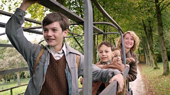 Udo (Alexander Kalodikis, 2.v.li.) vergnügt sich mit seinen Brüdern und seiner Mutter Käthe (Fanny Stavjanik).