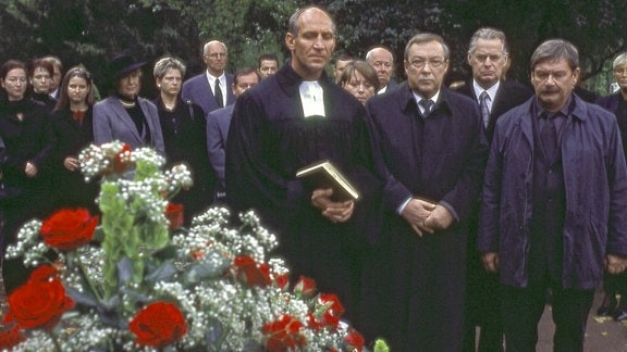 Die Kommissare Schmücke (Jaecki Schwarz) und Schneider (Wolfgang Winkler) tragen einen geliebten Menschen zu Grabe.