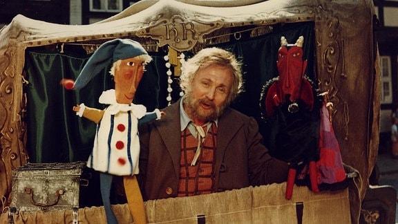 Meister Hans Röckle (Rolf Hoppe) spielt mit einer Puppe links und einer Teufelspuppe rechts durch das Fenster seiner Kutsche.