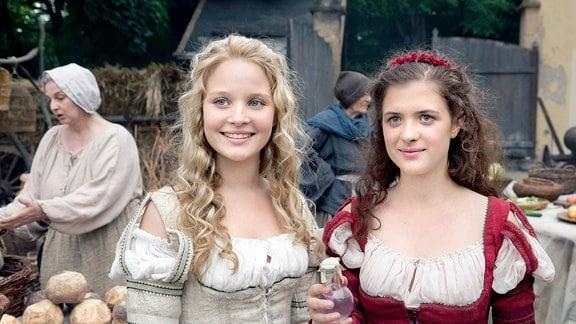 Schneeweißchen (Sonja Gerhardt, links) und Rosenrot (Liv Lisa Fries, rechts) verkaufen mit großem Erfolg selbst hergestelltes Rosenöl auf dem Markt.