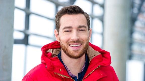 Sven Voss lächelt in einer roten Jacke in die Kamera.