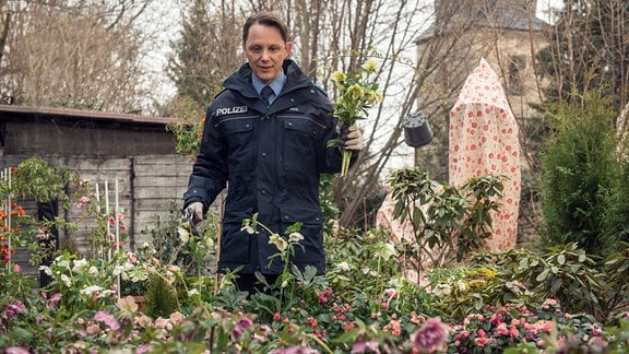 Lupo ( Arndt Schwering-Sohnrey) genießt seinen Garten. Er steht in einem Beet und hält einen Blumenstrauß in der Hand.