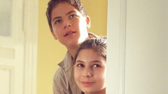 Drei Kinder im Alter von fünf bis dreizehn lugen um eine offene Zimmertür herum.
