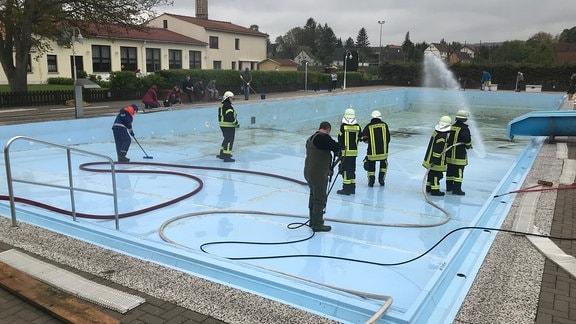 Mit kräftigem Strahl beseitigt die Feuerwehr auch den feinen Schmutz aus dem Freibad Hessen.