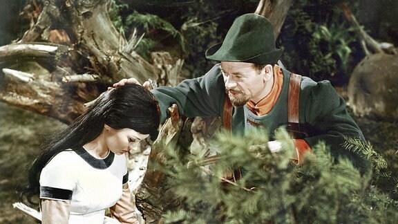 Der Jäger (Harry Hindemith) und Schneewittchen (Doris Weikow) sind in Gebüsch zu sehen.