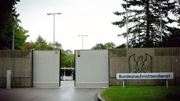 Eine Mauer umstellt das BND-Gebäude. Das eiserne Eingangstor geht auf.