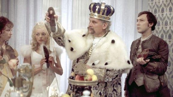 Der junge Soldat (Jaecki Schwarz, r.) wird vom König (Helmut Müller-Lankow, 2. v. r.) beauftragt, hinter das Geheimnis der allnächtlich zertanzten Schuhe seiner sieben Töchter zu kommen. Der Soldat verliebt sich in die jüngste Prinzessin (Blanche Kommerell, 2. v. l.).