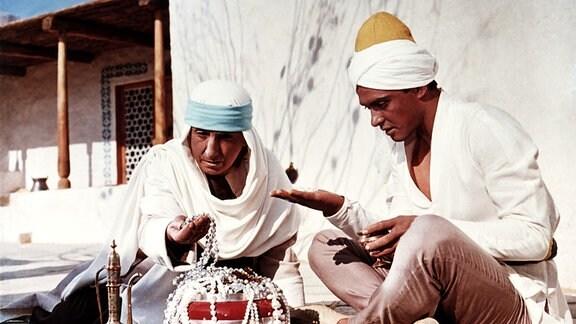 Erstaunt betrachten Aladin (Boris Bystrow, re.) und seine Mutter (E. Werulaschwili, li.) die Schätze, die ihnen ein angeblicher Onkel überbringen lässt.