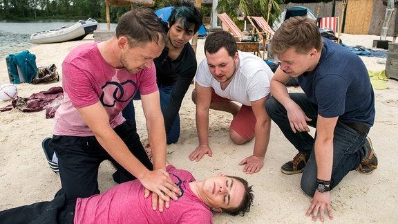 Max (Kai Malina, links) versucht knieend Oli (Marvin Linke, vorn, am Boden liegend.)  zu reanimieren (mit Komparsen).