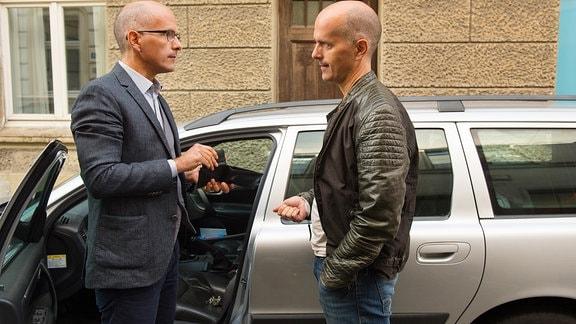 Tom (Christoph Maria Herbst, re.) steht seinem Bruder Matthias (Christoph Maria Herbst, li.) vor einem Auto gegenüber.