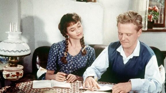 """Piroschka (Liselotte Pulver, links) mit """"Andy"""" (Andreas: Gunnar Möller) an einem Tisch  mit ausgebreiteten Büchern und Heften sitzend."""