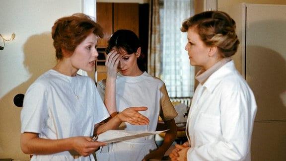 Frau Dr. Müller (Dorit Gäbler, r.echts) in Gespräch mit Krankenschwester Claudia Hoffmann (Monika Woytowicz, l.): beide in der typischen Berufsbekleidung der Mediziner.