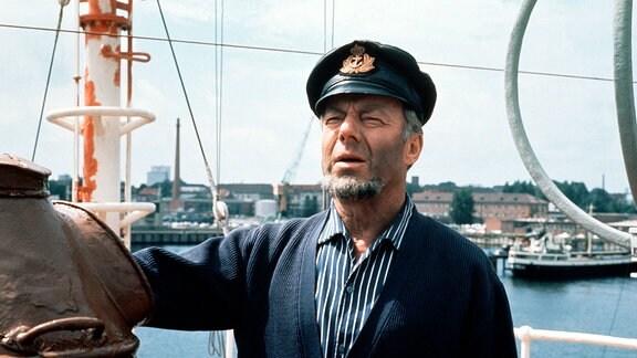Frachterkapitän Wilhelm Ebbs (Heinz Rühmann) auf einem Schiff  - im Hintergrund ist ein Hafen zu erkennen.