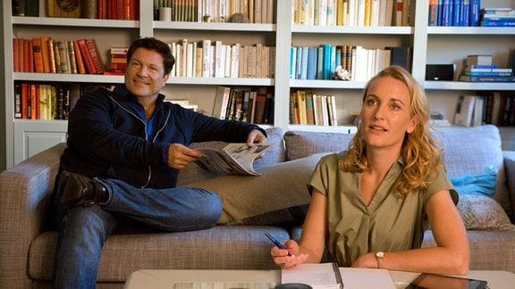 Christian (Francis Fulton Smith, l.) und Tanja (Christina Athenstädt, r.)sitzen in einer Wohnlandschaft..
