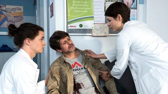 Dachdecker Stefan Lochner (Oliver Elias, Mitte) wird vonTom Zondek (Tilman Pörzgen, l.) und Dr. Theresa Koshka (Katharina Nesytowa, rechts) untersucht.