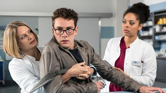 Markus Dahl (Louis Nitsche, Mitte) wird Dr. Ruhland (Gunda Ebert, links) umfasst. Vivi (Jane Chirwa, r.echts sieht zu. Markus Dahl  stützt sich imi den Armen ab.