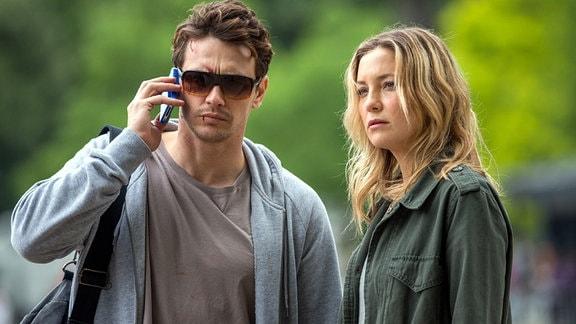 Das Ehepaar Tom (James Franco) und Anna Wright (Kate Hudson) stehen nebeneinander. Tom telefoniert.