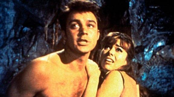 Der Amerikaner Herbert Brown (Michael Callan) und die Engländerin Elena (Beth Rogan) stehen umgeben von Dunkelheit im Lichtschein und schauen verängstigt nach oben.