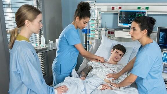 Simon (Aaron Hilmer, 2.v.r.) liegt im Bett.  Vivienne Kling (Jane Chirwa, 2.v.l.) und Dr. Leyla Sherbaz (Sanam Afrashteh, r.) stehen mit Sandra Funke (Henrike von Kuick, l.), an diesem Bett.