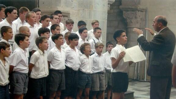 """Die """"Kinder"""" des Monsieur Mathieu singen im Chor. Mathieu dirogiert."""