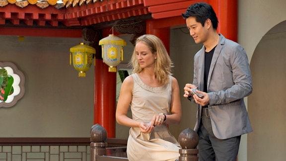 Anniela (Lara Joy Körner) sitzt auf einem Geländer; Dai Si (Jason Chan)  steht rechts neben ihr.