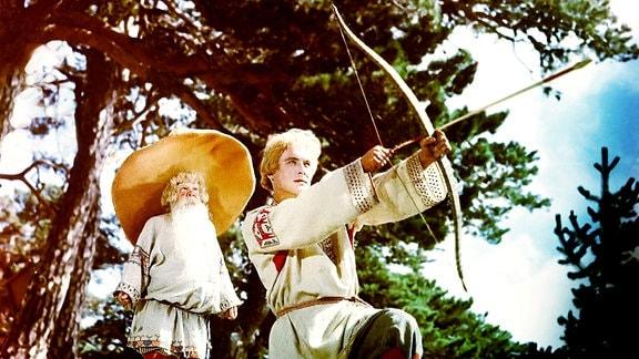 Iwan (S. Isotow, re.) und  ein kleines Waldmännlein (Galina Borisowa, li.) im Zauberwald. Iwan spannt einen Bogen mit einem Pfeil.