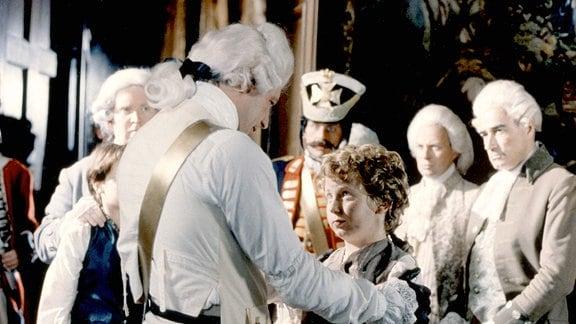 Der König (Andrew Bicknell, 3. v. li.) ist froh, und der Waisenjunge Tommi (Truan Munro, 2. v. li.) stehen sich gegenüber. Der König hat seine Hände auf Tommis Scgultern gelegt