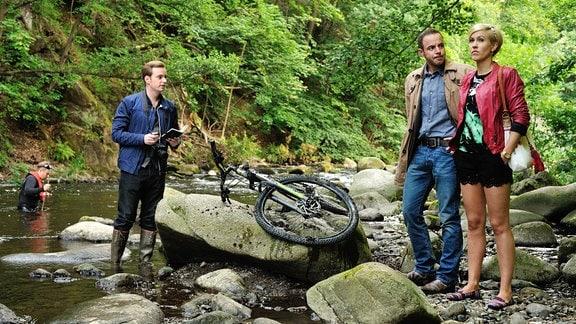 Klara (Wolke Hegenbarth) steht neben Hauptkommissar Paul Kleinert (Felix Eitner) und Jonas Wolter (Jan Niklas Berg) am Fluss, welcher aufrgund eines von Klara entdeckten, regunglosen Körpers untersucht wird.