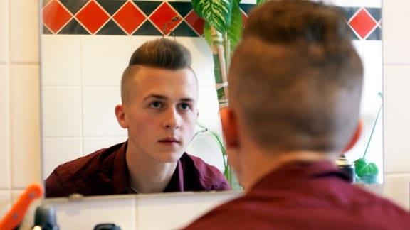 Haris schaut in den Spiegel.