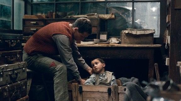 Pippig (Florian Stetter) hält den kleinen Jungen (Vojta Vomácka) versteckt.