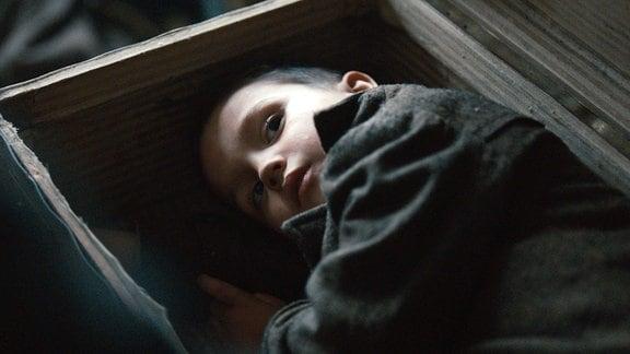 Kleiner Junge (Vojta Vomácka) versteckt sich in einem Koffer.